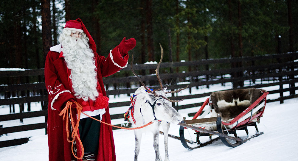Santa Claus waves as he stands with a reindeer and sled outside Rovaniemi, Finnish Lapland on December 15, 2011