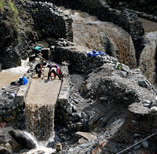 Local miners collect small rocks, as they mine for gold, from the waters that come from the mountains a day after Typhoon Haima struck Benguet province in northern Philippines, October 21, 2016