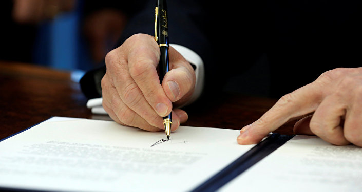 U.S. President Donald Trump signs a memorandum to security services directing them to defeat the Islamic State in the Oval Office at the White House in Washington, U.S. January 28, 2017