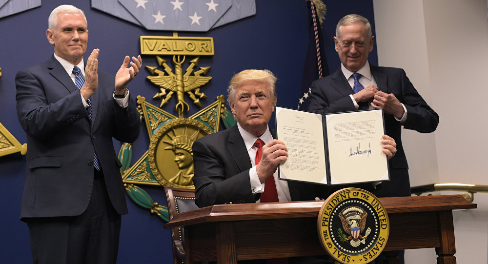 US President Donald Trump shows his signature on executive orders alongside US Defense Secretary James Mattis and US Vice President Muike Pence on January 27, 2017, at the Pentagon in Washington, DC