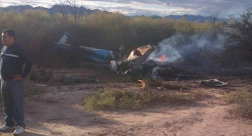 A man stands near one of two helicopters that crashed near Villa Castelli in the La Rioja province of Argentina, Monday, March 9, 2015. Two helicopters with passengers who were filming a documentary crashed Monday in the remote area of northwest Argentina, killing all 10 people on board both aircrafts, authorities said.