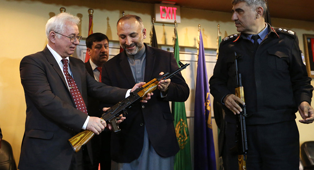 Russian Federation Ambassador, Alexander Mantytskiy, left, hands over an AK-47 to Afghan National Security Advisor, Mohammad Hanif Atmar, center, as the symbol of his country's military donation to the Afghan government, at Kabul International Airport, Wednesday, Feb. 24, 2016.