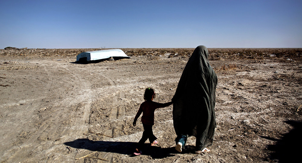 An Iranian woman walks with her daughter past an abandoned boat in Sikh Sar village at Hamoon wetland near the Zabol town, in southeastern province of Sistan-Baluchistan bordering Afghanistan on February 2, 2015.