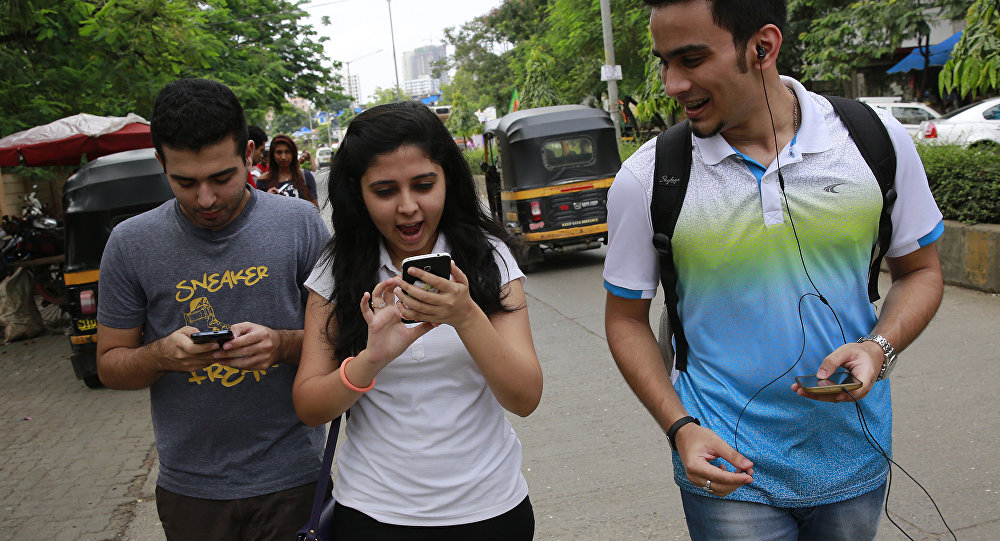 In this Sunday, July 24, 2016 photo, young Indians look at their screens as they play Pokemon Go in Mumbai, India