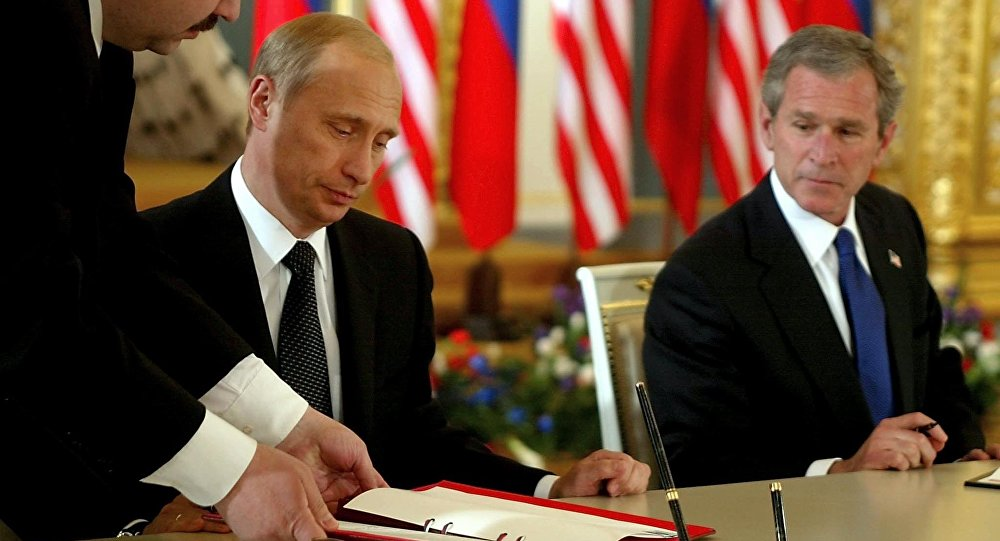 US President George W. Bush (R) looks on as Russian President Vladimir Putin (C) signs 24 May 2002 in St. Catherine's Room, the Kremlin in Moscow, Russia what the White House calls the Treaty of Moscow, a 10-year treaty binding the nations to reduce their nuclear stockpiles by about two-thirds - to a range of 1,700 to 2,200
