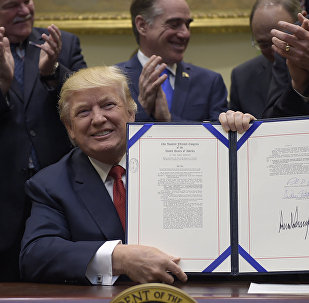 President Donald Trump hold up the Veterans Choice Program Extension and Improvement Act that he signed, Wednesday, April 19, 2017, in the Roosevelt Room of the White House in Washington