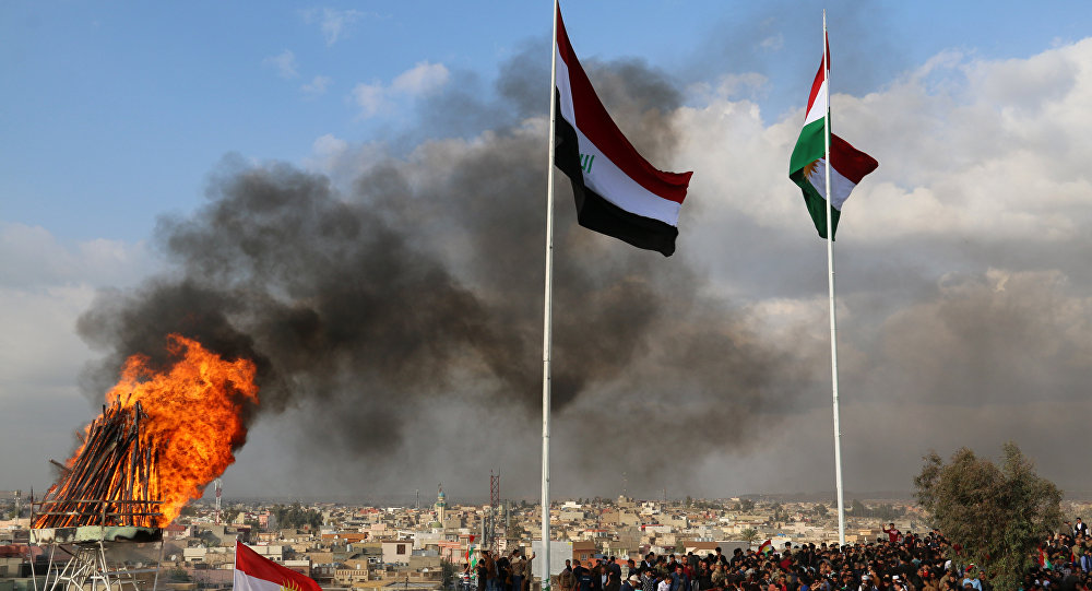The Kurdish and Iraqi flag sway in the wind as a bonfire burns during the Noruz spring festival celebrations in the northern city of Kirkuk, about 240 kilometres (150 miles) north of Baghdad on March 20, 2017