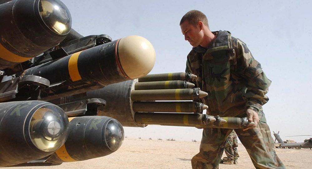 US Army armament crew specialist Michael Mayo, from Florida, loads the rocket pod of an an Apache AH-64D attack helicopter also armed with Hellfire missiles at left