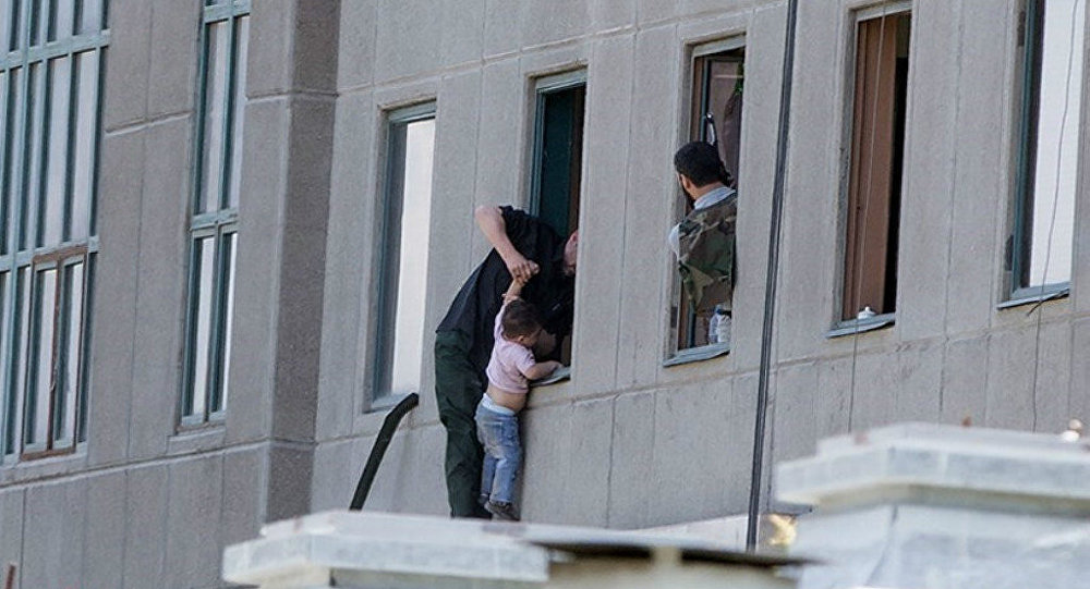 A boy is evacuated during an attack on the Iranian parliament in central Tehran, Iran, June 7, 2017