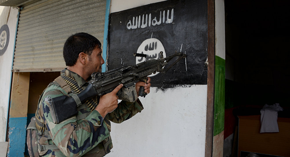 An Afghan soldier points his gun at an Islamic State group banner as he patrols during ongoing clashes in Kot District in eastern Nangarhar province
