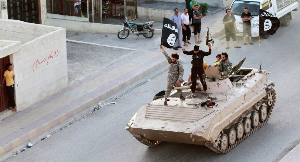 Militant Islamist fighters hold the flag of Islamic State (IS) while taking part in a military parade along the streets of northern Raqqa province in this June 30, 2014 file photo