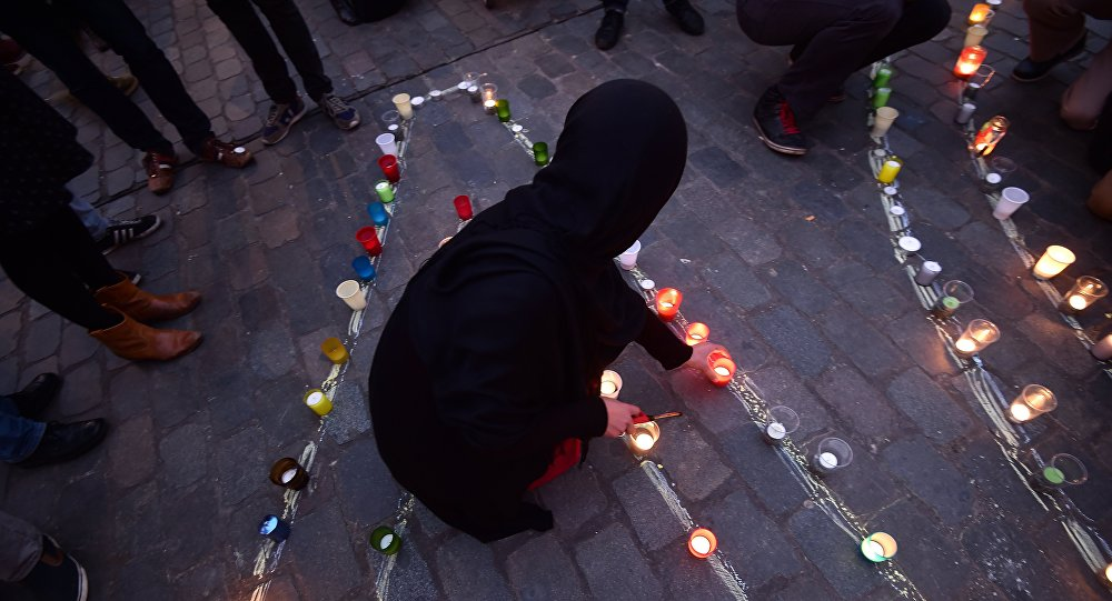 A person lights a candle during a candle light vigil to the victims of the Paris attacks in Brussels' Molenbeek district, on November 18, 2015.