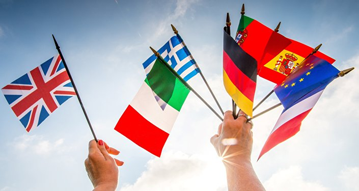A person holds European country flags in an hand and a United Kingdom flag in another.
