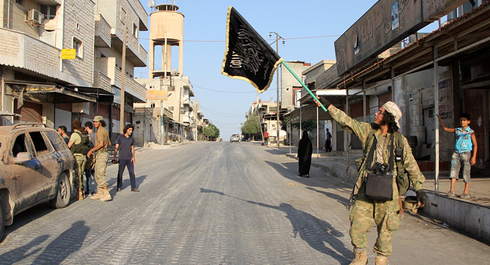 A fighter from the Jund al-Aqsa Islamist Brigade, raises an Islamist flag after taking control of the northern Syrian town of Tayyibat al-Imam, northwest of Hama from Syrian government forces on August 31, 2016